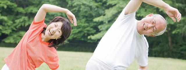 笑顔で体操をする中年の男女